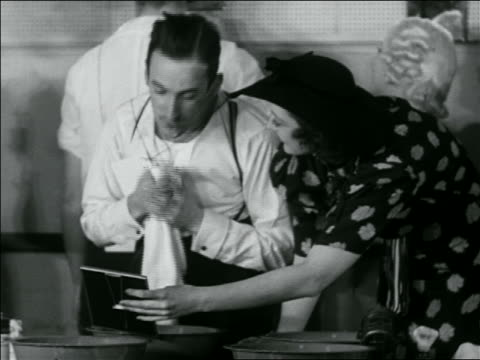 B/W 1936 young man wiping face after shaving contest as woman holds mirror for him / newsreel