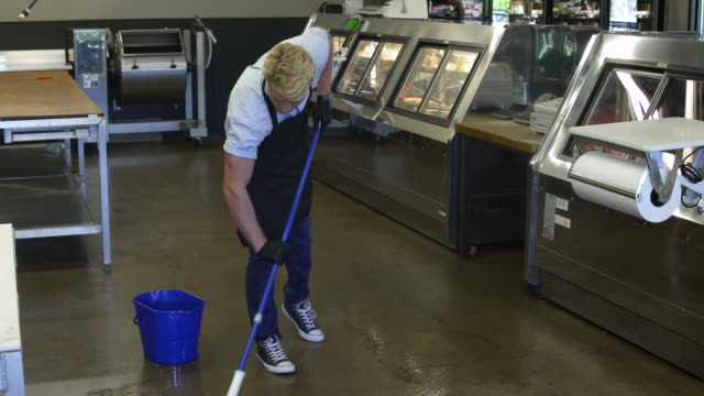 Young man wiping floor with a mop in a butcher shop