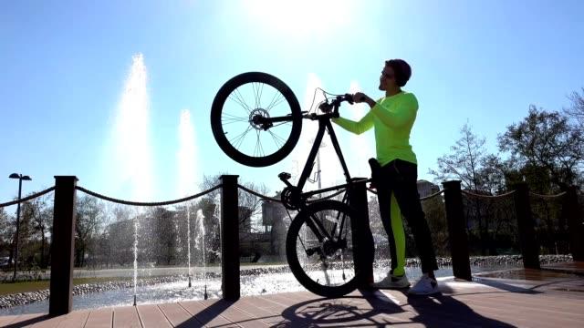 vidéos et rushes de jeune homme esprit exercice de vélo dans le parc - vêtements décontractés