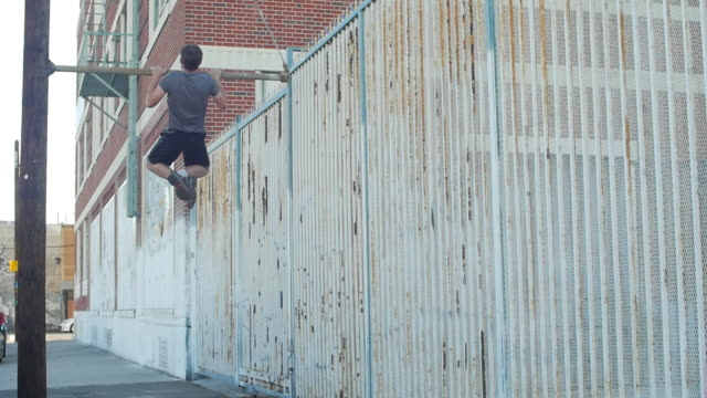 A young man with a beard doing pull-ups in urban environment.  - Slow Motion