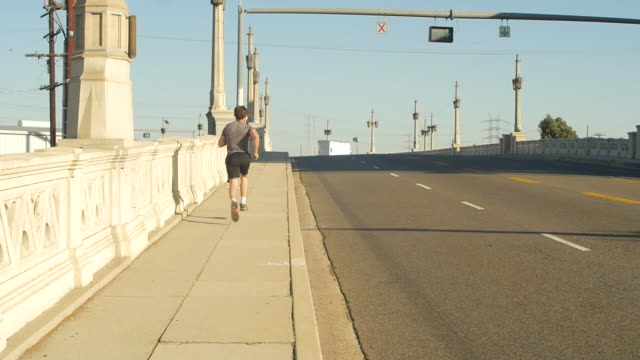 A young man with a beard going for a run in an urban environment,  - Slow Motion