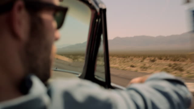 a young man with a beard rests his arm on the door of a convertible as it speeds along a desert highway. - man convertible stock videos & royalty-free footage