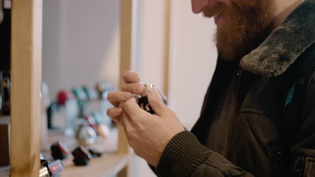 a young man with a beard shops at a bicycle store - partire bildbanksvideor och videomaterial från bakom kulisserna