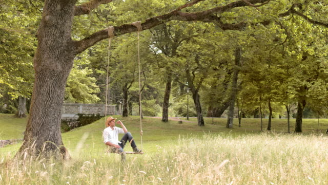 slo mo ds young man with a cowboy hat pondering on a swing - serene people stock videos & royalty-free footage