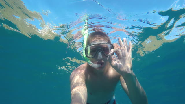 POV Young man with a diving mask giving thumbs up underwater