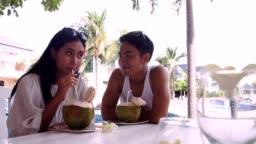 Young man with a girlfriend picnic party beach, Asian couples are sitting, relaxing and drinking coconut water on the poolside.