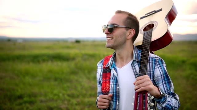 Junger Mann mit Gitarre in der Natur