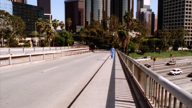 SLO MO, MS, Young man with afro hair walking on overpass, office buildings in background, Los Angeles, California, USA