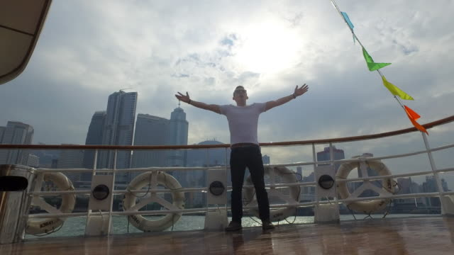 vidéos et rushes de young man with arms outstretched on deck of ferry with hong kong skyline behind - hong kong, china - les bras écartés