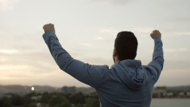 Young man with arms raised