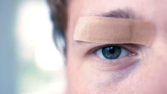 目に絆創膏と若い男 - 絆創膏点の映像素材/bロール