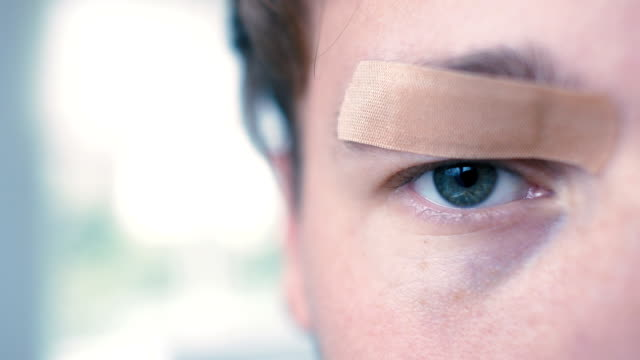 Young Man with Bandaid over Eye