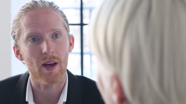 young man with beard and hair tied back talking to colleague at work - hair back stock videos & royalty-free footage