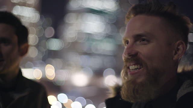 young man with beard looks at camera and smiles with friend on city balcony at night. - 30 34 jahre stock-videos und b-roll-filmmaterial