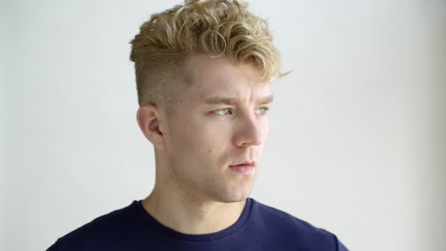 vidéos et rushes de young man with blonde hair looking away, studio shot. - en désordre