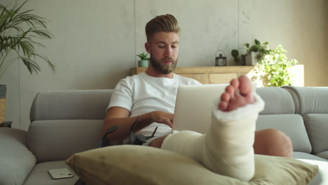 young man with broken leg using laptop at home - human leg stock videos & royalty-free footage
