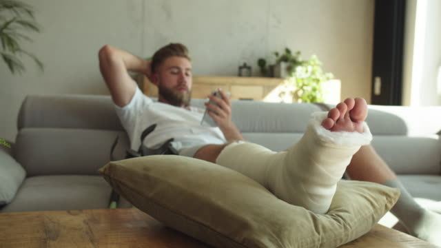 young man with broken leg using smart phone - human leg stock videos & royalty-free footage