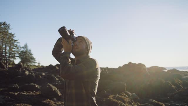 young man with camera captures nature photography on rocky coastal terrain. - カメラマン点の映像素材/bロール