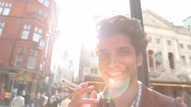 cu. young man with cigarette smiles and laughs at camera on london street corner. - smoking stock videos & royalty-free footage