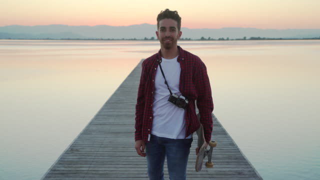 young man with cool attitude, casual clothes, plaid shirt and skate posing and looking at camera. old-fashioned analog photography camera at sunset in the pier of a river. casual hipster clothes and cool attitude. - plaid shirt stock videos & royalty-free footage