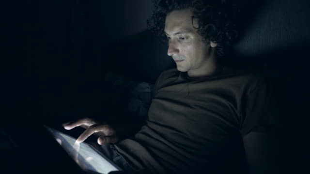 Young man with digital tablet at night.