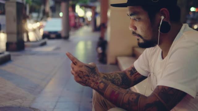 市のイヤホンを持つ若者。 - 聞く点の映像素材/bロール