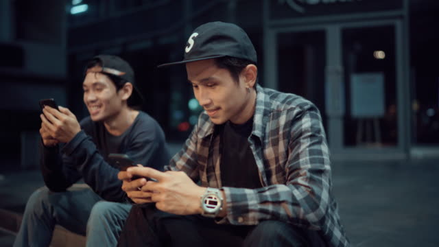 young man with friend skateboarding and using smart phone at night street - thai ethnicity stock videos & royalty-free footage