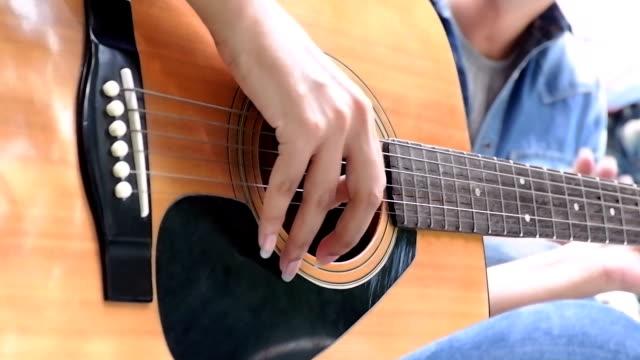 vídeos de stock, filmes e b-roll de jovem com namorada tocando guitarra dentro de casa. formato hd. - violão acústico