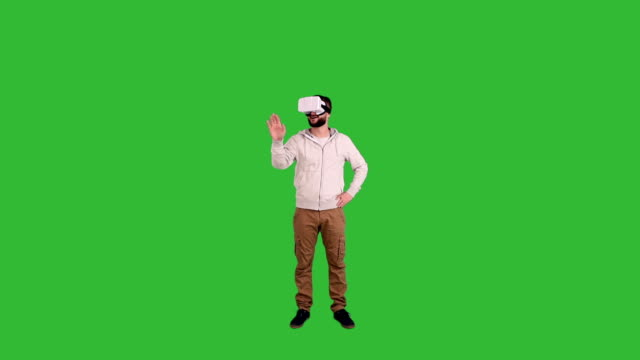 young man with glasses of virtual reality shows a copy space and the thumb on a green background - illusion stock videos & royalty-free footage
