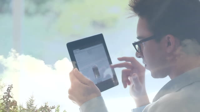 Young man with glasses using digital tablet, cloud reflections.