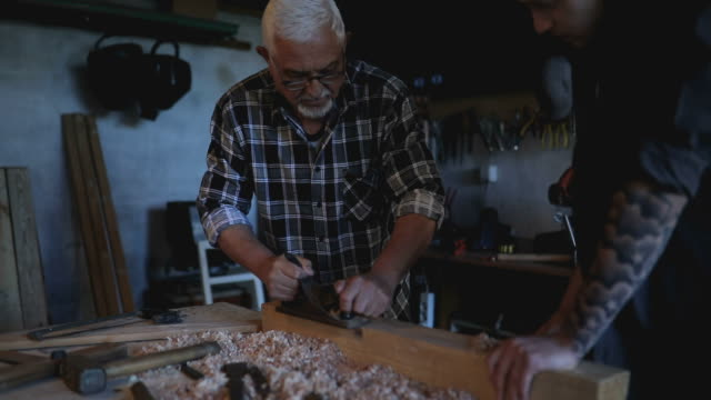 Young man with grandpa at workshop
