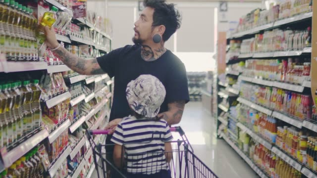 young man with little baby boy in grocery store - for sale stock videos & royalty-free footage