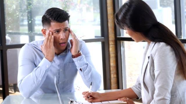 vidéos et rushes de jeune homme avec des maux de tête migraine s'entretient avec la femme médecin - se tenir la tête entre les mains