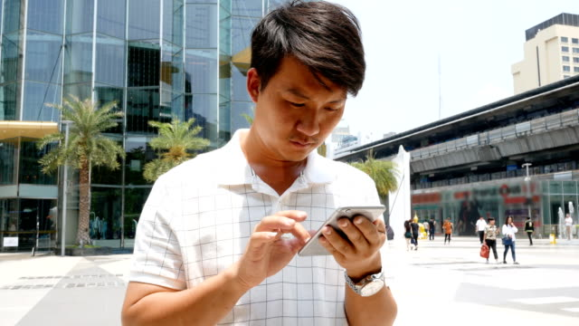 young man with mobile phone in the street - holing stock videos & royalty-free footage