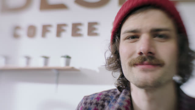 cu slo mo. young man with mustache smiles and laughs at camera in hip local coffee shop. - moustache stock videos & royalty-free footage