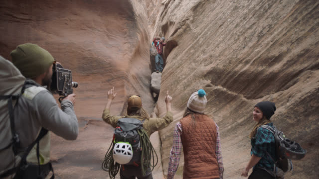 stockvideo's en b-roll-footage met young man with old film camera documents friends on climbing adventure in moab. - electrical equipment
