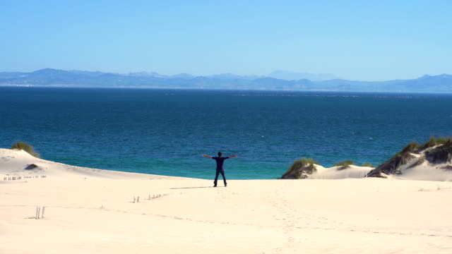 a young man with open arms from a dune sand with ocean and africa coast behind him - one mid adult man only stock videos & royalty-free footage