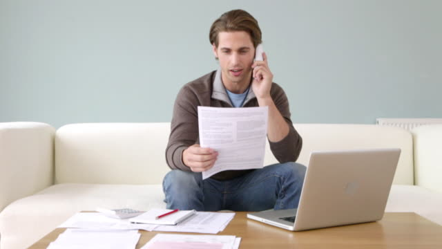 Young man with paperwork on the phone