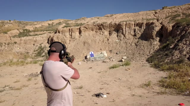 young man with proper safety gear shooting an assault rifle in a remote shooting range - target shooting stock videos & royalty-free footage