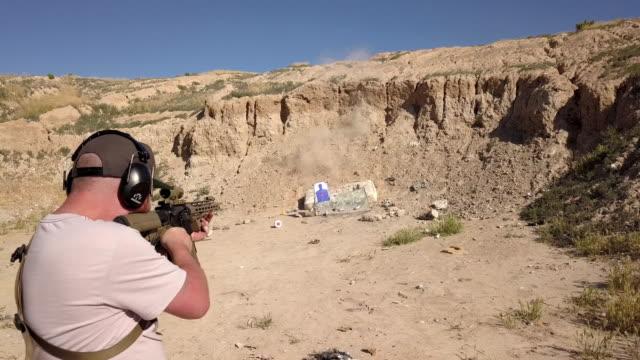 junger mann mit der richtigen sicherheitsausrüstung schießt ein sturmgewehr in einem abgelegenen schießstand - pistolenschießen stock-videos und b-roll-filmmaterial