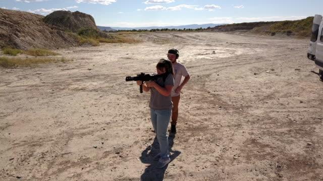 Junger Mann mit der richtigen Sicherheitsausrüstung schießt ein Sturmgewehr in einem abgelegenen Schießstand