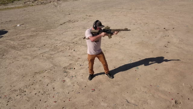 適切な安全装備を持つ若い男は、遠隔射撃場でアサルトライフルを撃つ - クレー射撃点の映像素材/bロール