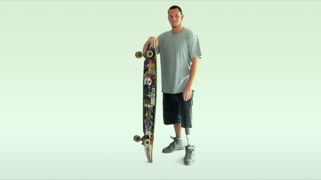 ws young man with prosthetic leg holding skateboard / wilmington, north carolina, usa - artificial limb stock videos & royalty-free footage