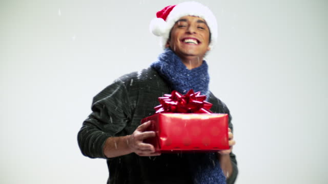 young man with santa hat and gift dancing in snow fall - santa hat stock videos & royalty-free footage