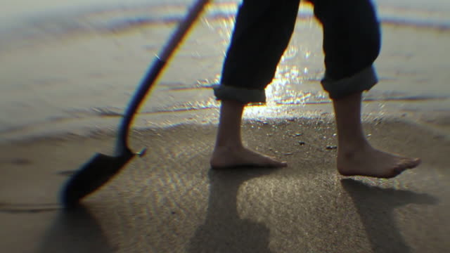 pov young man with shovel walking on wet sand, low section / los angeles, california, usa - nur junge männer stock-videos und b-roll-filmmaterial