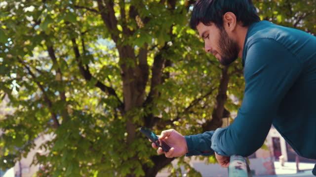 vidéos et rushes de jeune homme avec un téléphone intelligent dans un parc en plein air - se reposer