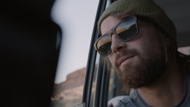 young man with sunglasses stares out car window. - barba peluria del viso video stock e b–roll