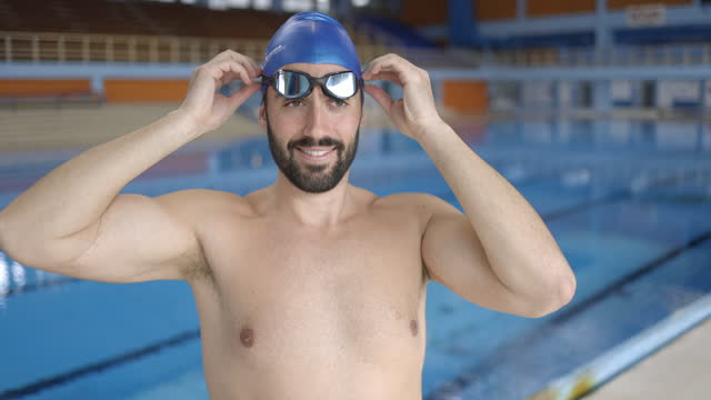 young man with swimming cap standing on poolside and putting on swimming googles - swimming cap stock videos & royalty-free footage
