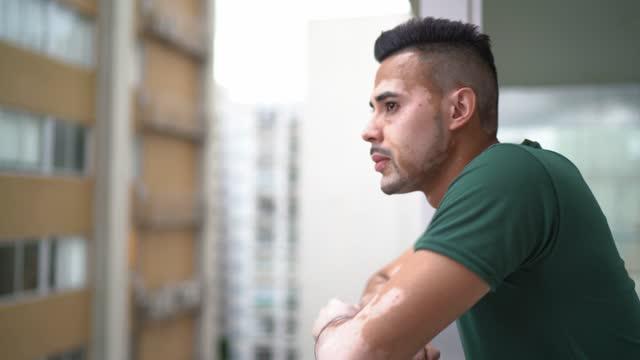 vidéos et rushes de jeune homme avec le vitiligo regardant la vue de ville - profil