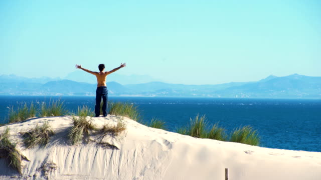 a young man, without t-shirt, upping his arms from a dune sand with ocean and africa coast behind him - one mid adult man only stock videos & royalty-free footage